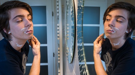 boy shaving while looking in mirror